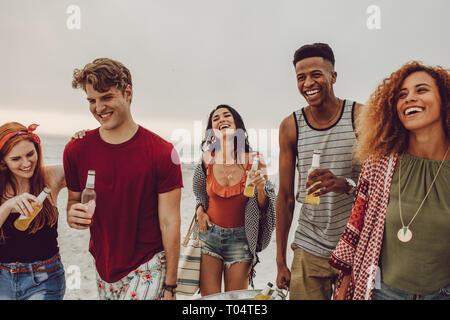 Groupe de personnes transportant des boissons à remous pour partie sur la plage. Groupe varié de jeunes la marche à l'extérieur et avoir des boissons.