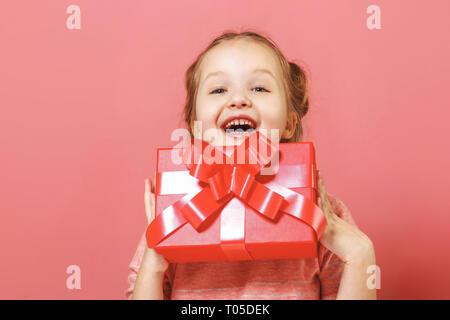 Closeup portrait of a cute little girl avec brioches de cheveux sur un fond rose. L'enfant est titulaire d'un fort avec un cadeau