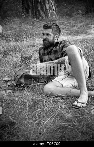 Chemise à carreaux en tourisme tenir mug. Hipster avec longue barbe et vous détendre sur l'herbe verte. Homme barbu avec thé ou café tasse en forêt. Camping, boire et Banque D'Images