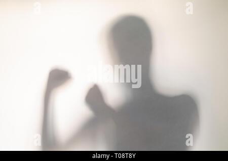 Dans la lutte contre l'homme poser derrière le rideau. Mains et trouble figure humaine l'abstraction. Banque D'Images