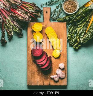 Les betteraves en tranches colorées avec des greens d'ingrédients sur une table de cuisine à découper, la vue de dessus. L'alimentation végétarienne et la cuisine saine Banque D'Images