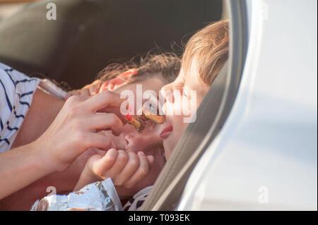 Jeune mère de nourrir son petit fils avec un bonbon de chocolat dans... Banque D'Images