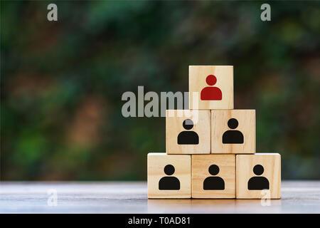 Pensez différemment et concept de leadership. Blocs de bois empilés avec une icône de l'homme rouge et noir sur la table en bois et de l'espace vide sur la gauche. D Banque D'Images