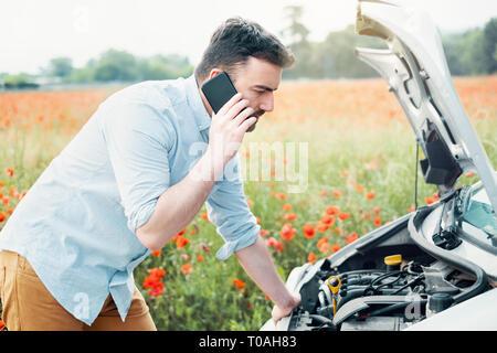 Souligné pilote après panne de voiture appelant l'assistance routière Banque D'Images