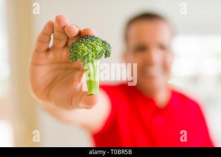 MIiddle age man showing morceau de brocoli Banque D'Images