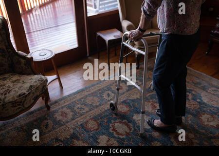 Active senior woman walking with walker dans la salle de séjour à la maison Banque D'Images