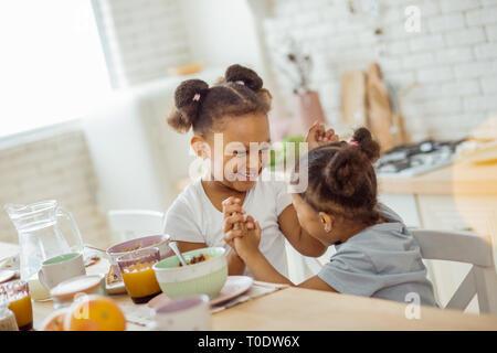 Jolies filles aux cheveux bouclés tenant leurs mains ensemble