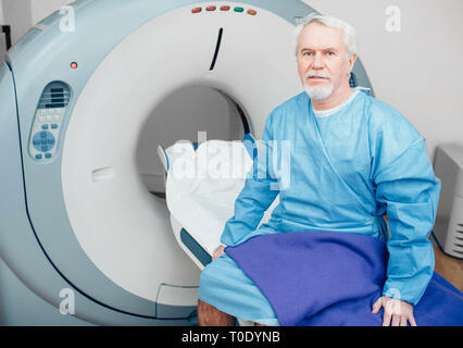 Senior man sitting on table du scanner. en attente de CT scan
