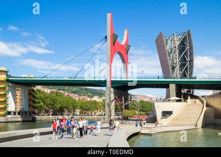 Les touristes près de la sculpture d'araignée 'maman' par Louise Bourgeois sous le pont La Salve à l'extérieur Musée Guggenheim de Bilbao, en Espagne. Banque D'Images