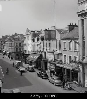 Années 1950, Cherbourg, France, vue de dessus d'une rue de ville montrant voitures françaises de l'époque stationné à côté de la vente au détail, y compris Andre magasin de chaussures et la Dauphone, Les mures de Cherbourg. Banque D'Images