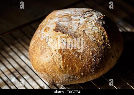 Du pain frais au levain fait de se reposer sur une grille. Concept de cuisson fait maison. Du pain artisanal avec golden croûte croustillante.
