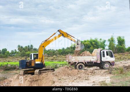 La charge de la machine excavatrice jaune sol dans un camion-benne at construction site Banque D'Images