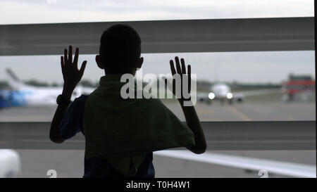 Boy stands près de la fenêtre à l'aéroport et il s'intéresse aux avions, le garçon rêve de devenir un pilote, s'amuser