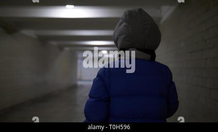 Adolescents promenades à travers un étroit tunnel sombre en hiver, tient quelque chose dans sa main, vue arrière Banque D'Images