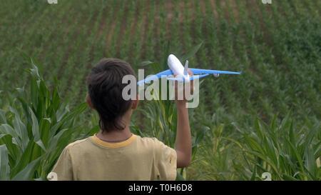 Garçon jouant avec un jouet avion sur un champ de maïs, le garçon rêve de devenir un pilote