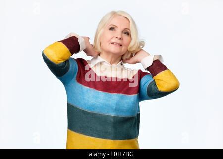 Femme blonde de toucher le visage doucement et regardant les satisfaits de l'appareil photo