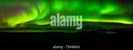 Un large panorama de la northern lights sur les montagnes en West-Iceland, reflétée dans la mer Banque D'Images