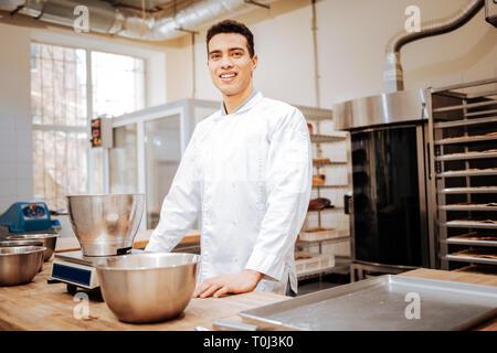 Dark-haired chef portant uniforme blanc debout dans la cuisine