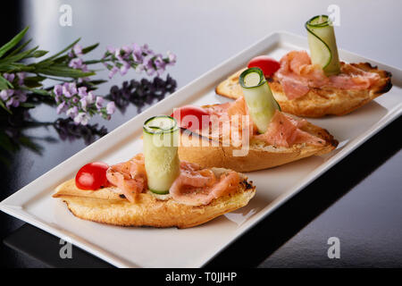 Filet de poisson sur du pain sur une plaque blanche avec des fleurs lilas Banque D'Images