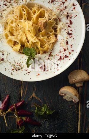 Carbonara pâtes dans une assiette blanche avec des champignons sur une table en bois noir Banque D'Images