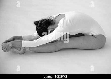 Sa formation de flexibilité. Ballerine doing stretching exercice. Ballerine en classe de ballet. Jolie femme en vêtements de danse. La pratique de la danse classique Banque D'Images