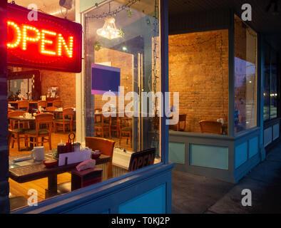 Vue d'un café de l'extérieur de l'intérieur à la nuit en hiver Banque D'Images
