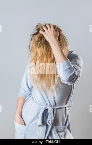 Jeune femme en peignoir de jouer avec ses cheveux mouillés lavés. Banque D'Images