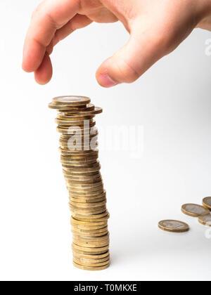 L'argent, financier, la croissance de l'entreprise concept, la main de l'homme mettre de l'argent monnaie pour pile de pièces sur fond blanc copy space Banque D'Images