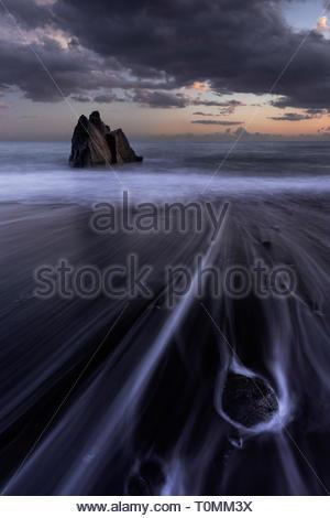 Praia Formosa au coucher du soleil, une plage d'un simple rocher sur la gauche et les formations rocheuses sur la droite, l'île de Madère, São Martinho, Portugal Banque D'Images