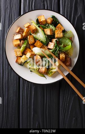 Tofu sauté avec bok choy et les graines de sésame sur une assiette sur la table. Haut Vertical Vue de dessus Banque D'Images
