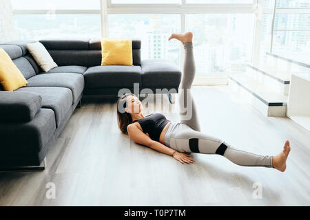 Femme adulte ABS Formation abdominaux Faire des ciseaux avec les jambes