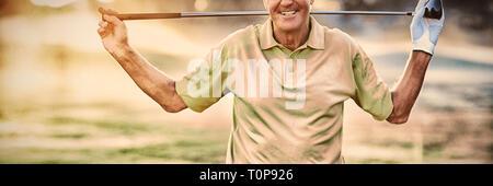 Portrait of smiling mature golfer transporter golf club