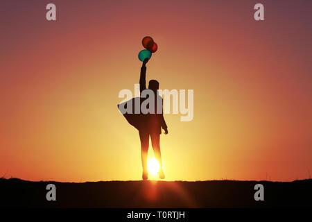Girl jumping avec des ballons au coucher du soleil, des ballons colorés, incroyable coucher du soleil Ciel volant dans le ciel Banque D'Images