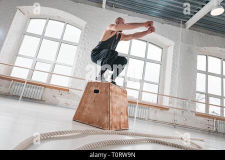 Saut à l'athlète masculin remise en forme fort squat dans la salle de sport. Homme fort de faire un saut de l'exercice dans la salle de lumière Banque D'Images