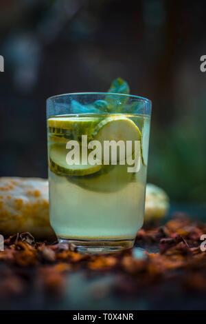 Close up de concombre frais dans un verre d'eau sur la surface en bois avec des tranches de citron et de concombre et quelques glaçons. Banque D'Images