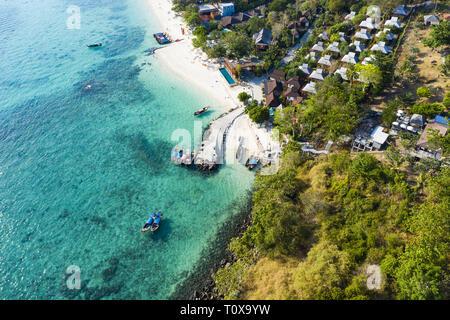 Superbe vue aérienne d'un petit port avec des bateaux à longue queue flottant sur une mer turquoise.