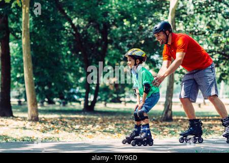 Père et fils de roller en parc.