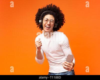 Beau jeune homme dans les écouteurs d'écouter de la musique sur le téléphone Banque D'Images