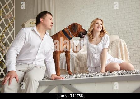 Happy young couple avec leur animal assis sur le plancher du salon.