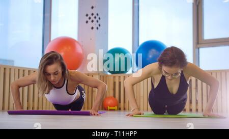 Les jeunes femmes chargées de fitness dans le studio. Faire push-ups Banque D'Images