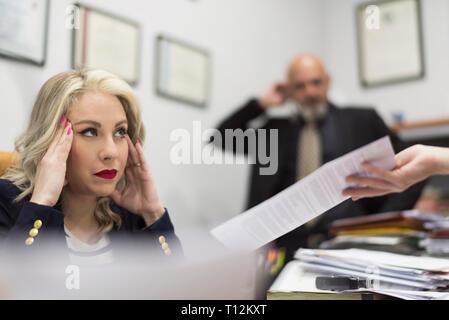 Female office worker a souligné devant une grande charge de travail de bureau et documents