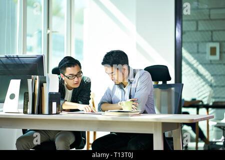 Deux jeunes dirigeants de sociétés asiatiques travaillant ensemble discuter de plan d'affaires de l'office.