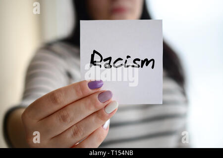 Jeune fille triste montre un autocollant blanc. Caucasian brunette tenant une feuille de papier avec un message. Le racisme Banque D'Images