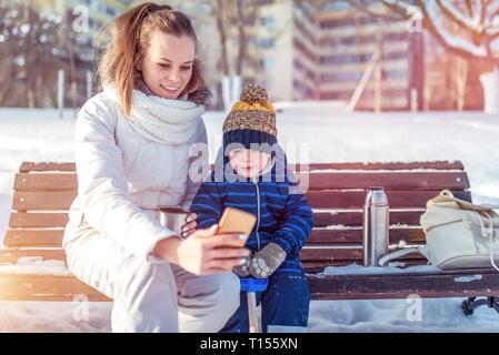 Maman prend une photo et montre smartphone à son enfant un petit garçon. En hiver dans la ville, sur un banc, l'air glacial frais en décembre et janvier. Banque D'Images