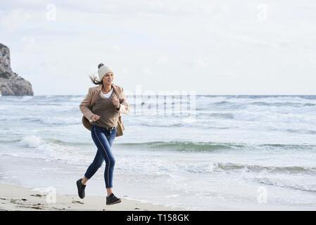 L'Espagne, Minorque, senior woman jogging sur la plage en hiver Banque D'Images