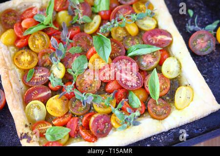 Vue en hauteur sur la tarte aux tomates cerises sur la pâte feuilletée avec feuilles de basilic et d'origan Banque D'Images