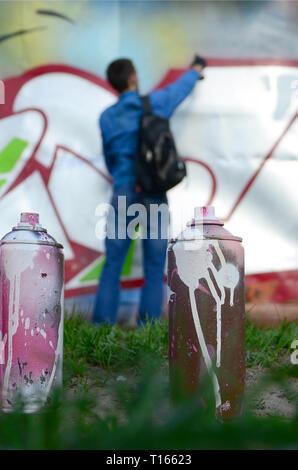 Quelques pots de peinture utilisée dans le contexte de l'espace avec le mur sur lequel le jeune homme attire un grand dessin graffiti. Art moderne de l'établissement w