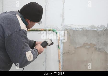 Un vieil ouvrier perce un trou dans un mur en polystyrène pour l'installation ultérieure d'une armature en plastique goujon. La création de trous dans le mur avec un Banque D'Images