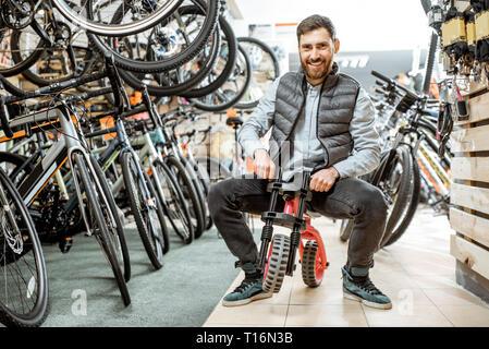Portrait d'un homme drôle équitation children's location dans le magasin avec les vélos et les équipements sportifs