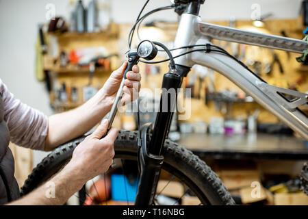 Réparateur au service d'une location, la vérification d'une pression de l'air dans l'amortisseur pneumatique d'une fourchette dans l'atelier